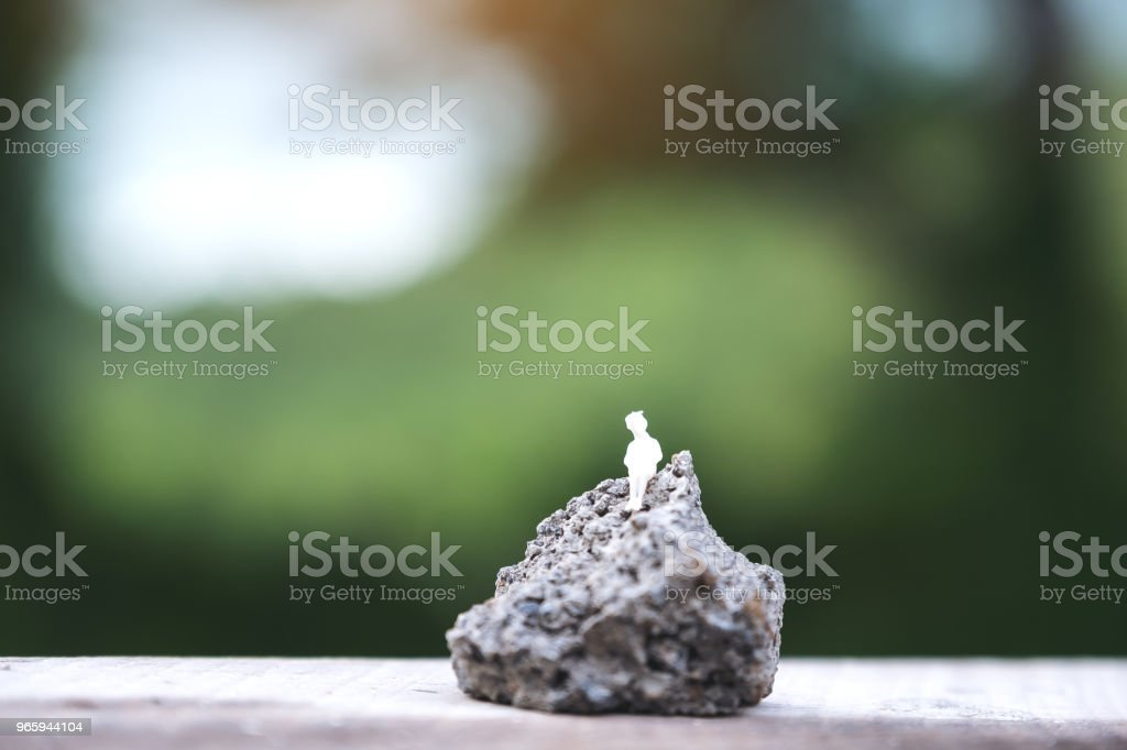 Closeup image of miniature figure model of a lonely woman sitting on the rock with blur background - Royalty-free Adult Stock Photo