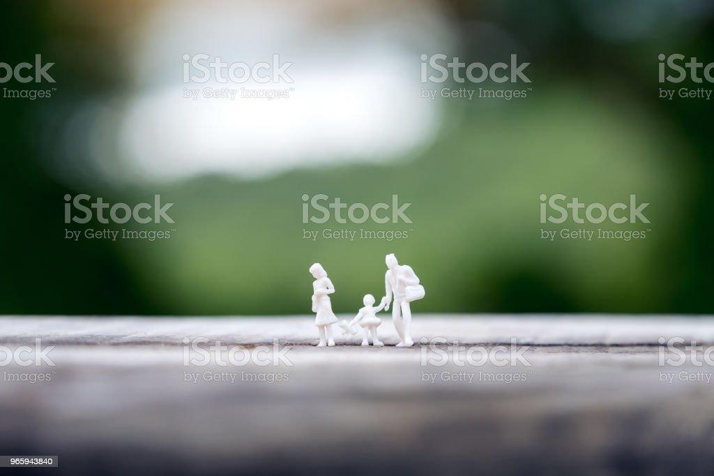 Close-up beeld van miniatuur figuur model van vader, moeder en dochter samen lopen op houten tafel met achtergrond wazig - Royalty-free Baby Stockfoto