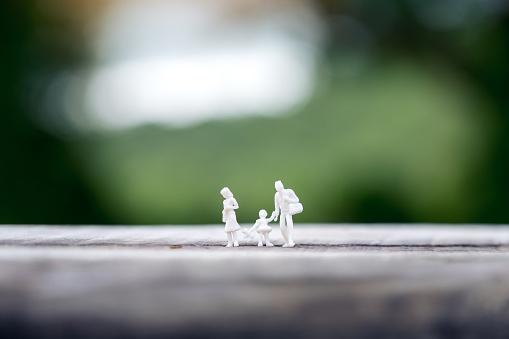 Closeup Beeld Van Miniatuur Figuur Model Van Vader Moeder En Dochter Samen Lopen Op Houten Tafel Met Achtergrond Wazig Stockfoto en meer beelden van Baby