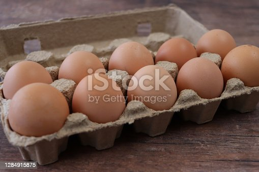Stock photo showing close-up view of batch of ten, brown chicken eggs in  an open disposable cardboard egg box on wooden table top.