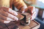 Closeup image of people playing and building round wooden puzzle game