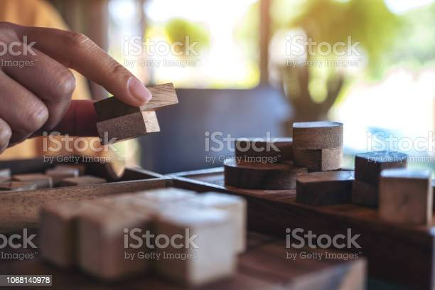 Closeup image of people playing and building round wooden puzzle game picture id1068140978?b=1&k=6&m=1068140978&s=612x612&h=2ujznjyfdkqa4livycyft9gnx7dugjttncqq0ff9zui=