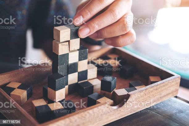 Closeup image of people playing and building wooden puzzle game picture id957116734?b=1&k=6&m=957116734&s=612x612&h= l1gqeddjcxfgmxwig9betuden9rjddmuun0zmo0ncg=