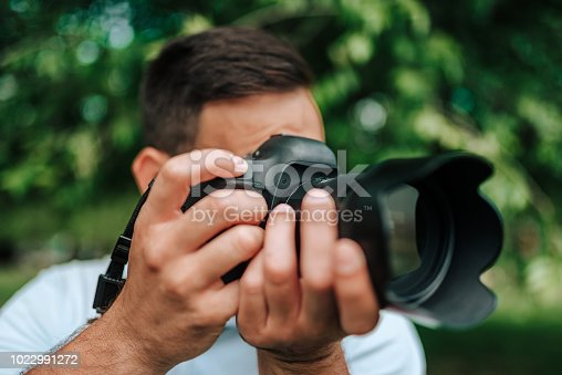 Close-up image of professional photographer outdoors.