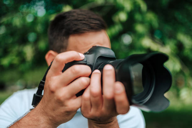 Close-up image of professional photographer outdoors. Close-up image of professional photographer outdoors. digital single lens reflex camera stock pictures, royalty-free photos & images
