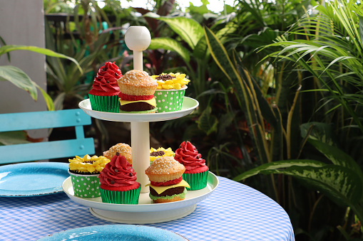 Close-up image of round table covered with blue and white checked table cloth and tiered, white cake stand, mini cheeseburgers, sunflower and watermelon design cupcakes, afternoon tea on outdoor balcony