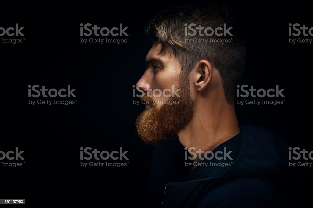 Close-up image of serious brutal bearded man on dark background stock photo