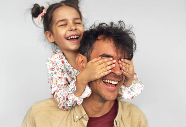Closeup image of smiling little girl embraces her dad, shares love together. Handsome man playing with kid peekaboo game. Playful daughter cover the eyes with hands of her father for a surprise. stock photo