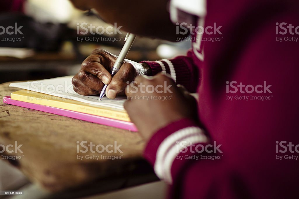 Closeup image of South African girl writing at her desk stock photo