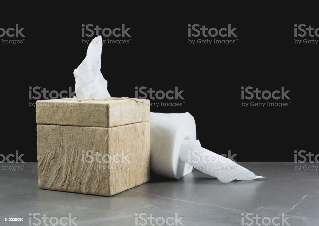 Close-up image of toilet papers roll with box on the table with dark background. stock photo