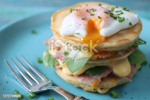 Stock photo showing a close-up, elevated view of a turquoise plate containing a stack of mini pancakes, served florentine eggs benedict style against a blue wood background. Layers of pancake, bacon, spinach leaves, hollandaise sauce and poached egg beside a metal fork.