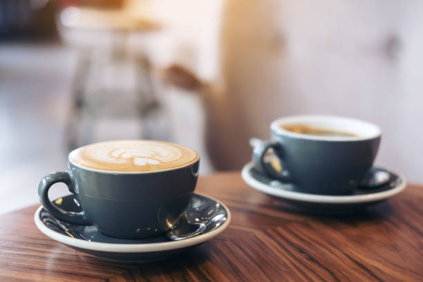 Closeup image of two blue cups of hot latte coffee and Americano coffee on vintage wooden table in cafe stock photo
