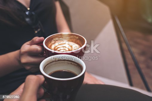 istock Closeup image of two people clinking coffee cups in modern cafe 879527280