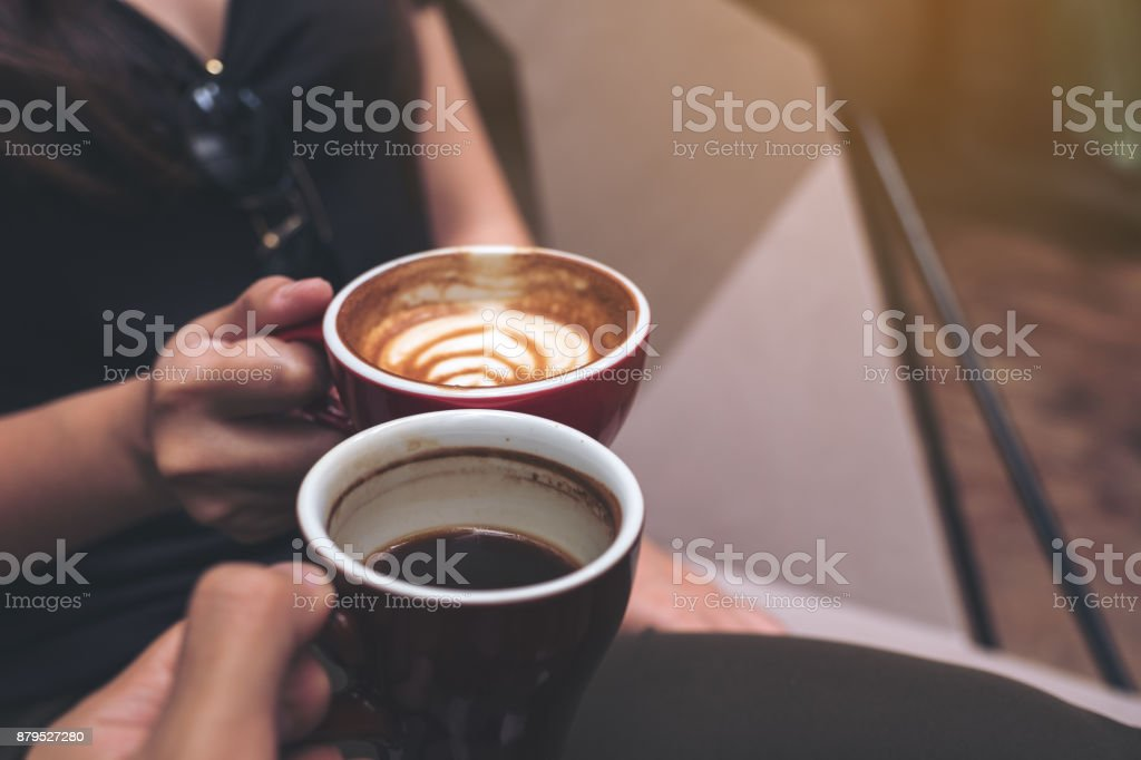 Closeup image of two people clinking coffee cups in modern cafe stock photo