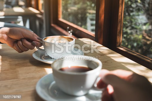 Closeup image of two people holding and drinking coffee in the morning