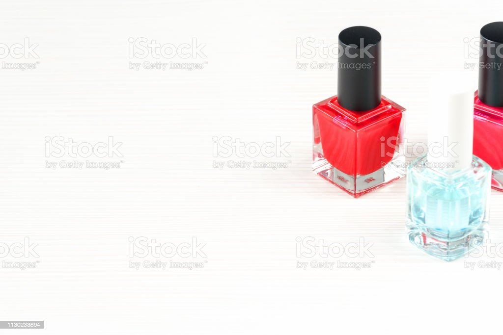 Close-up image of Two Red nail polish bottles and one colorless nail...