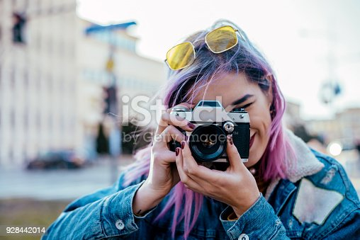 Close-up image of urban female photographer using camera.