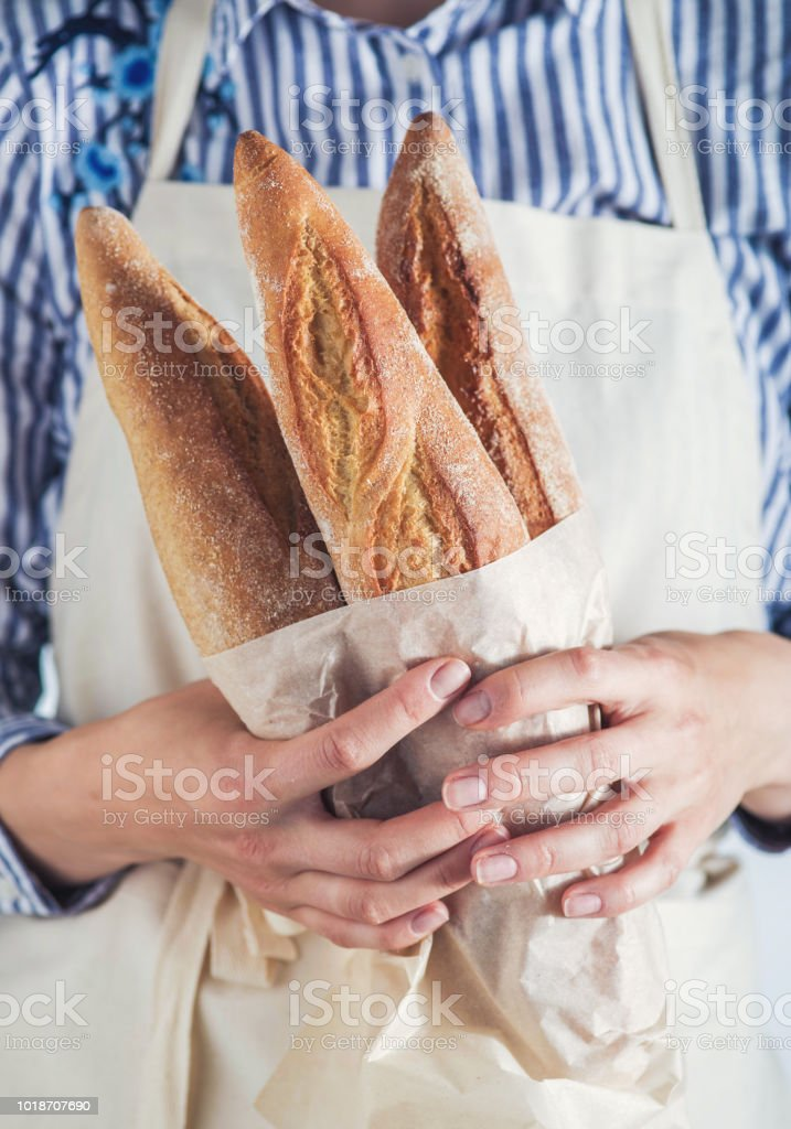 Close-up image of woman holding package of fresh baguettes. стоковое фото