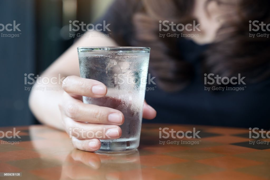 Closeup image of woman's hand holding a glass of cold water on table - Royalty-free Adult Stock Photo