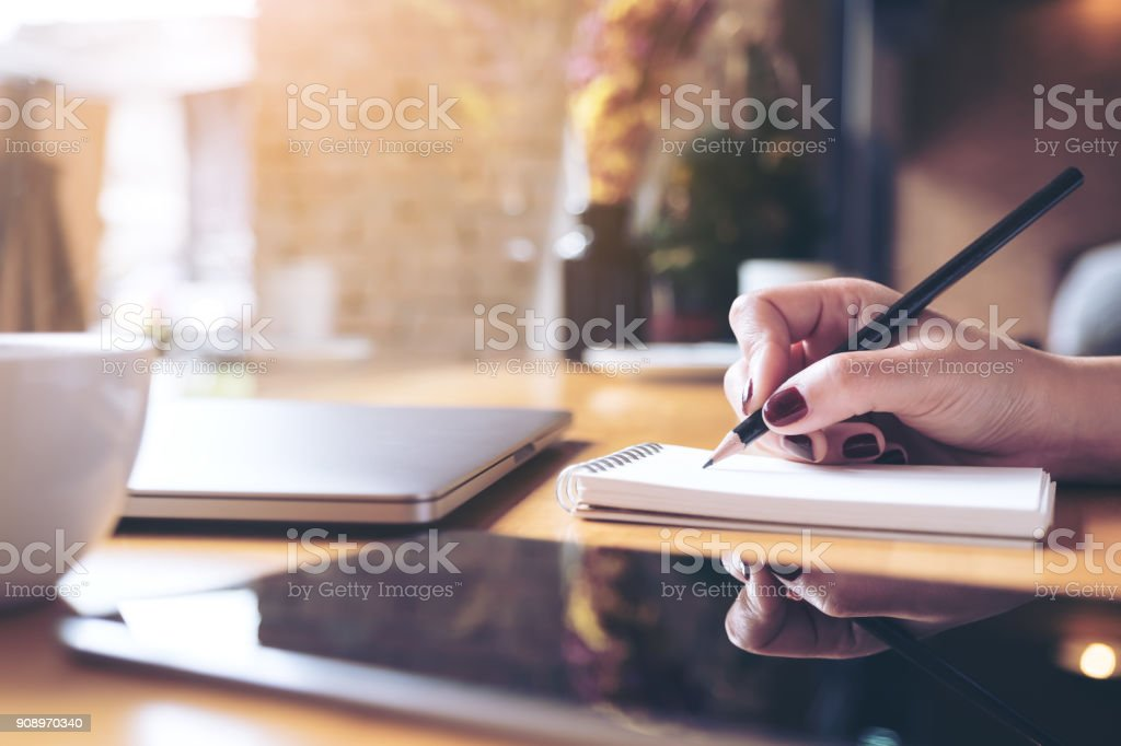 Closeup image of woman's hand writing on a blank notebook with laptop , tablet and coffee cup on wooden table background stock photo