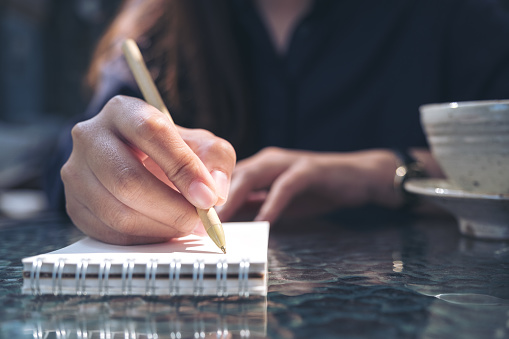 Closeup image of woman's hand writing on blank notebook with coffee cup on the table background