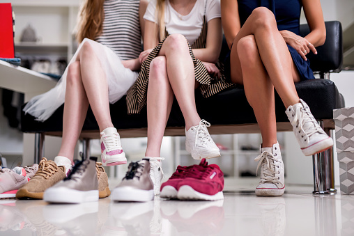 Close-up image of women sitting with legs crossed trying on new sneakers in shopping center