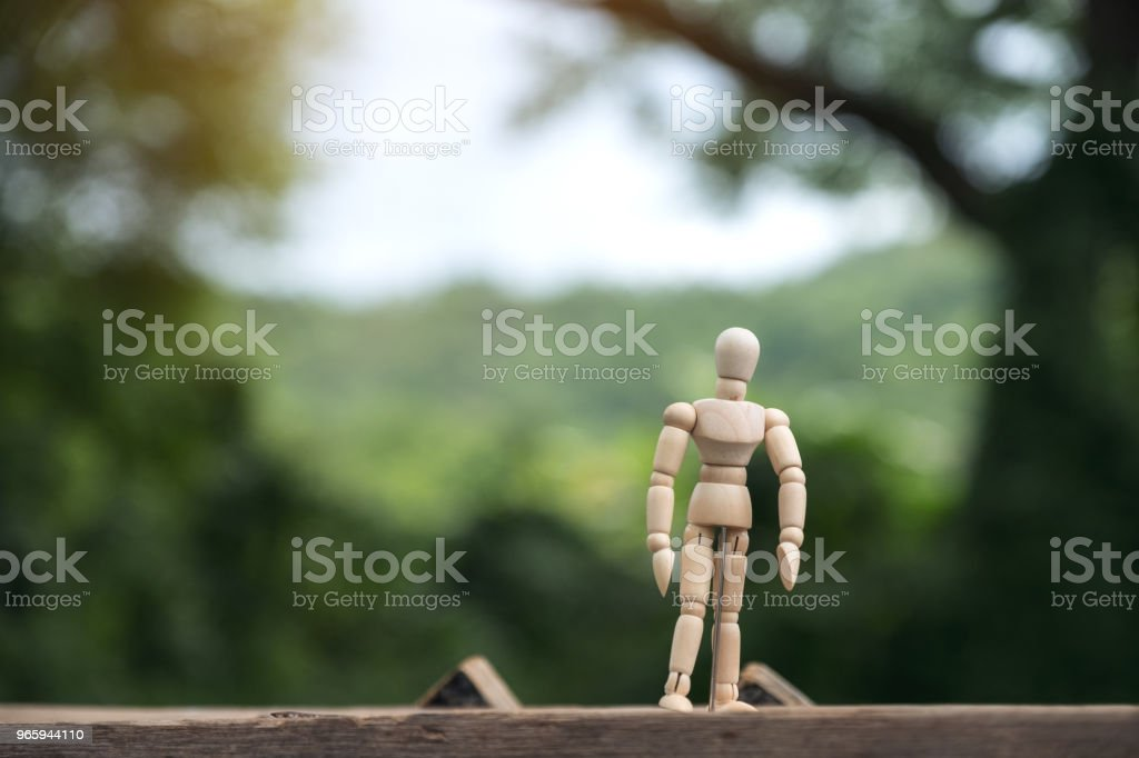 Closeup image of wooden figure model of a man standing on wooden table with blur background - Стоковые фото Взрослый роялти-фри