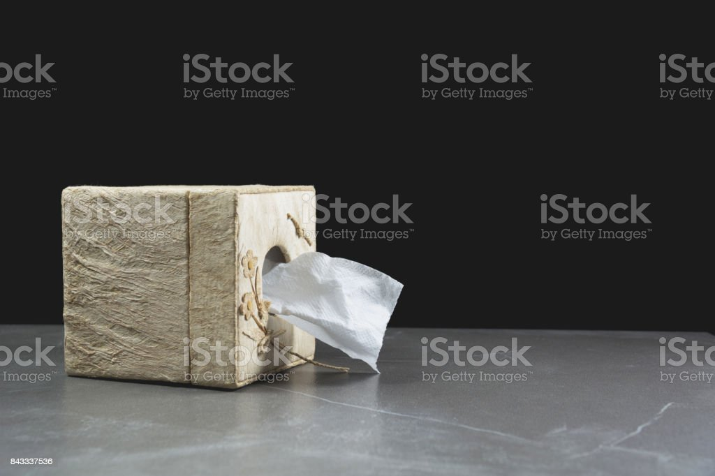 Close-up image one of toilet papers roll in box on the table with dark background. stock photo