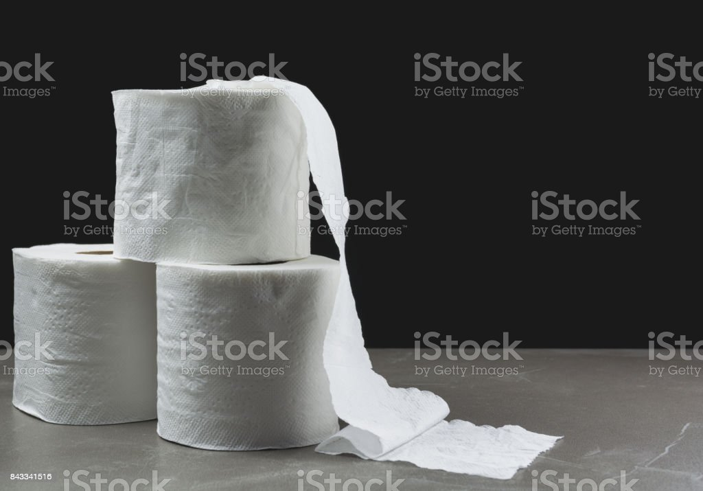 Close-up image stack of toilet papers roll on the table with dark background. stock photo