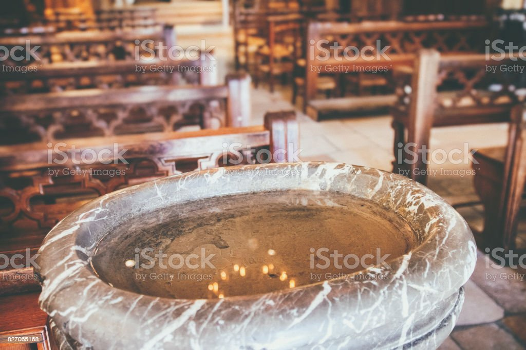 Close-up in selective focus on baptismal font in marble with holy water and light reflections near entrance of beautiful french church stock photo