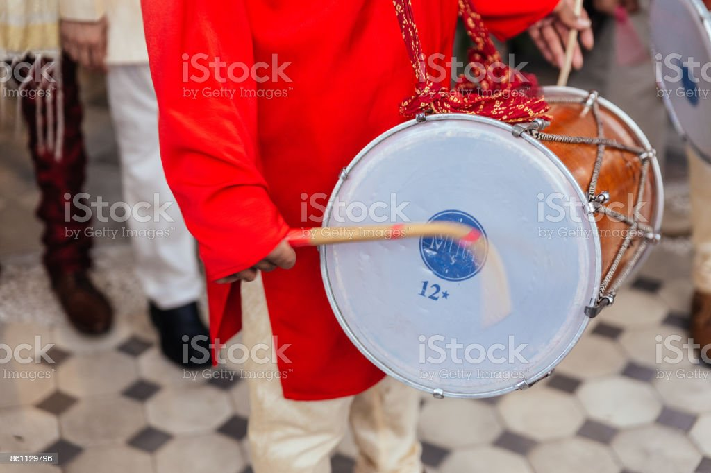 Close-up Indian musician guy drumming Dhol and wearing red Bandhgala at Indian wedding ceremony in Bangkok, Thailand. stock photo
