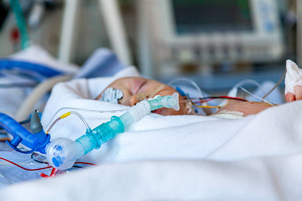 Close-up, Infant child in intensive care unit after surgery. stock photo