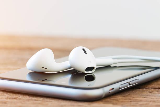 zbliżenie iphone'a i earpods urządzenia na stole - akcesorium osobiste zdjęcia i obrazy z banku zdjęć