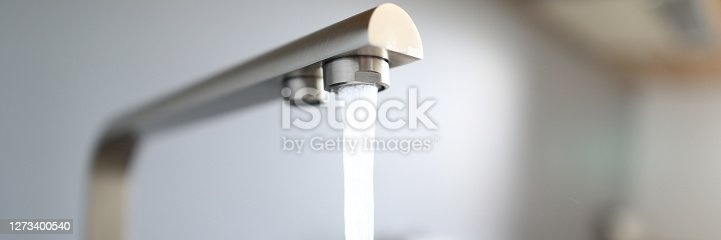 istock Close-up jet water from silver tap in kitchen 1273400540