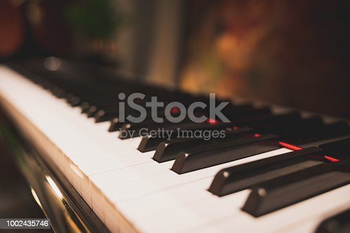Close-up keyboard of a piano in romantic classic atmosphere, depth of field effect. Music instrument, pianist, song composer, hobby, musical education, or wedding event concept