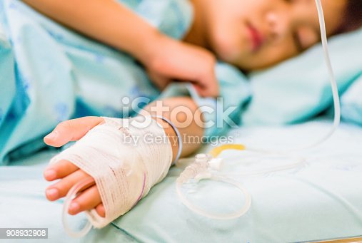 istock Closeup kid hand  sleeps on a bed in hospital with saline intravenous. 908932908