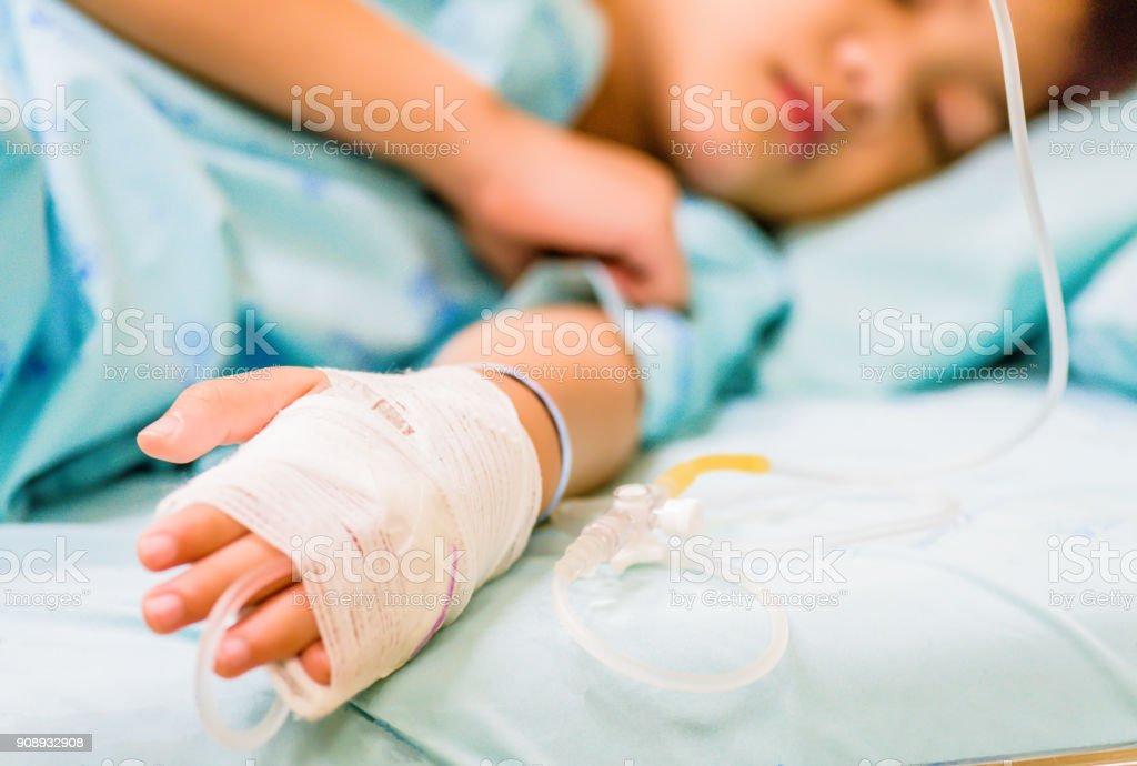 Closeup Kind Hand schläft auf einem Bett im Krankenhaus mit Kochsalzlösung intravenös. – Foto