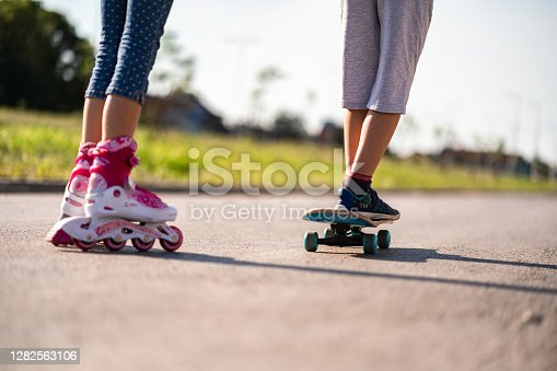 Closeup of a boy riding his skateboard and girl riding her roller skates