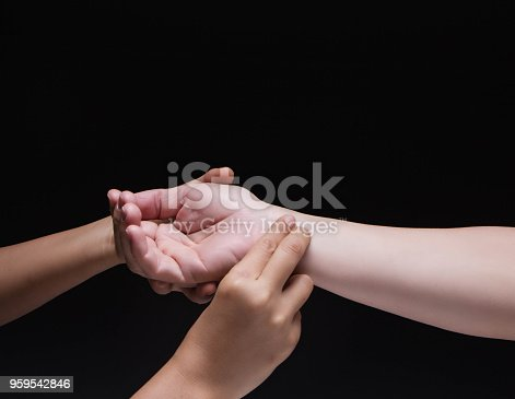1035928092istockphoto Closeup lady hand is checking heart rate by press finger to arm of the man, 959542846