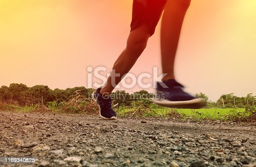 Close-up Legs of Asian young man is jogging on dirt road in the park. Healthy lifestyle.