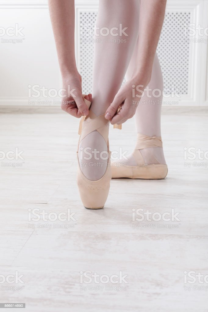 Closeup legs of ballerina puts on pointe ballet shoes stock photo