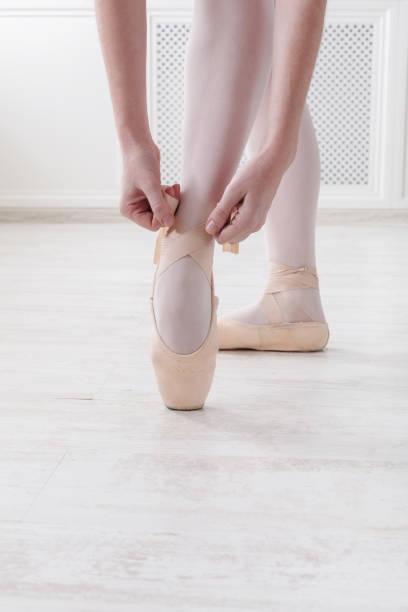 Closeup legs of ballerina puts on pointe ballet shoes stock photo