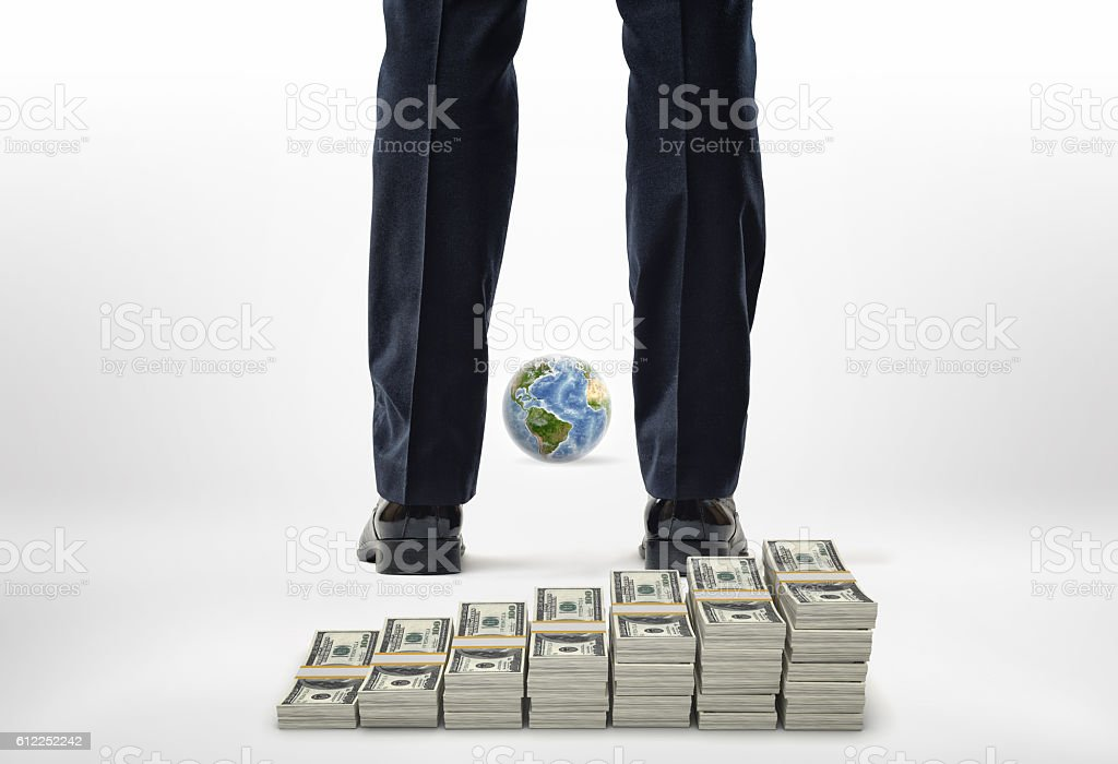 Close-up legs with packs of dollars and small globe. stock photo
