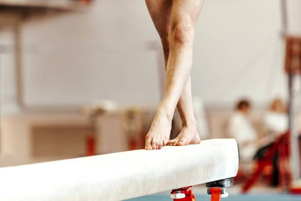 closeup legs women gymnasts exercises on balance beam stock photo