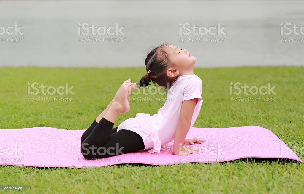 Close-up little asian child girl doing yoga in the public park. stock photo