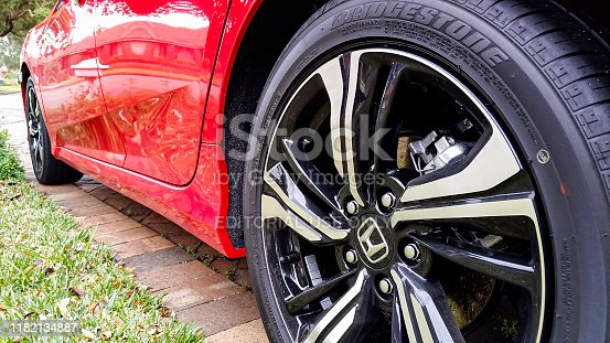 Sydney, Australia - Aug 6, 2016: Close-up low angle view of the back wheel of a 10th Generation Honda Civic vehicle in Rallye Red. Feature wheel, brake caliper, tyre and a