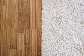 Close-up luxury white carpet on laminate wood floor in living room, interior decoration