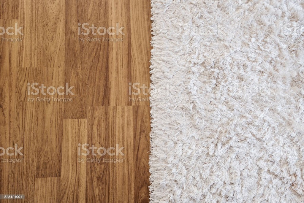 Close-up luxury white carpet on laminate wood floor in living room, interior decoration stock photo