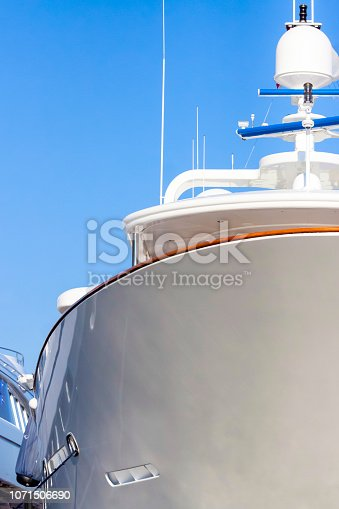 Closeup luxury yacht at harbour, blue sky background with copy space, vertical composition with copy space