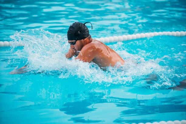 primer plano atleta masculino natación pecho en la piscina durante los campeones. - vuelta completa fotografías e imágenes de stock